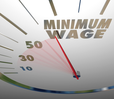 Minimum Wage words on a speedometer or gauge measuring the rising amount of pay or earning for working a low level job